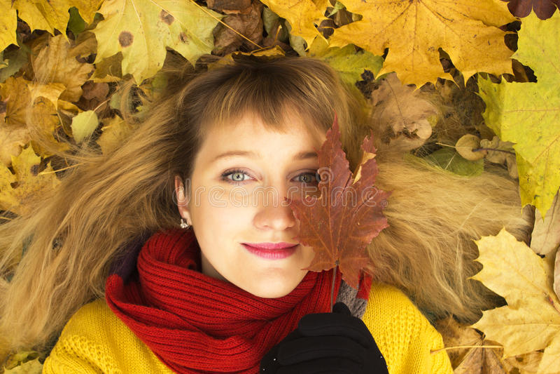 Молодая красивая девушка лежа на листьях и усмехаться осени стоковые изображения