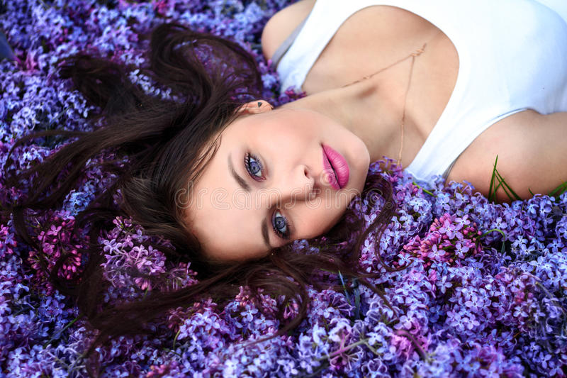 Молодая красивая девушка лежит на цветках сирени стоковая фотография rf