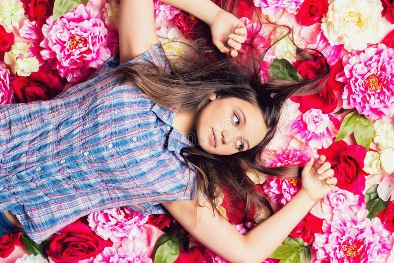 Молодая красивая девушка лежит на цветках стоковое изображение rf