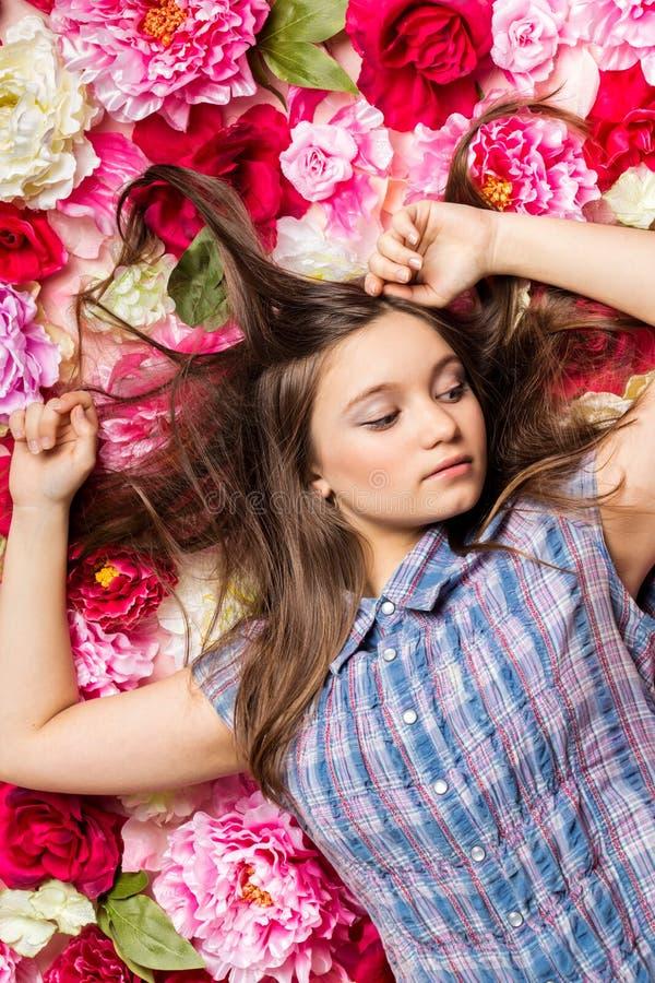 Молодая красивая девушка лежит на цветках стоковые фотографии rf