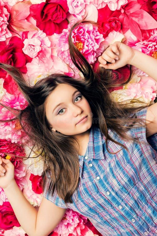 Молодая красивая девушка лежит на цветках стоковая фотография rf