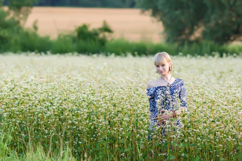 Молодая красивая девушка идет на blossoming поле гречихи стоковое изображение rf