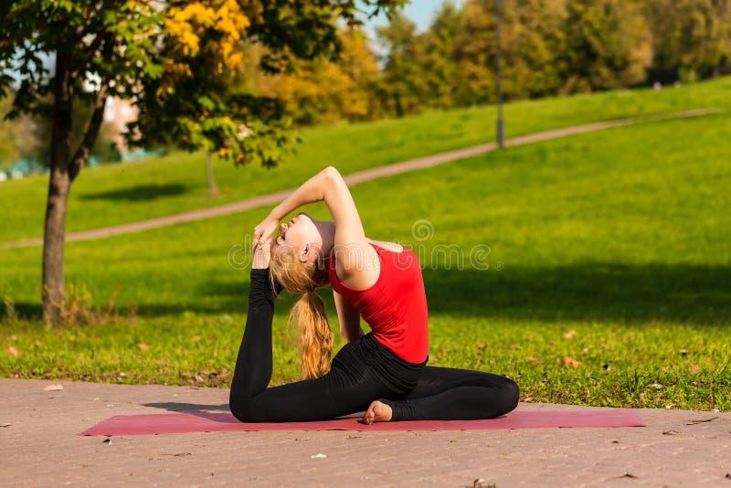 Молодая красивая девушка приниманнсяая за йога, outdoors в парке стоковое изображение