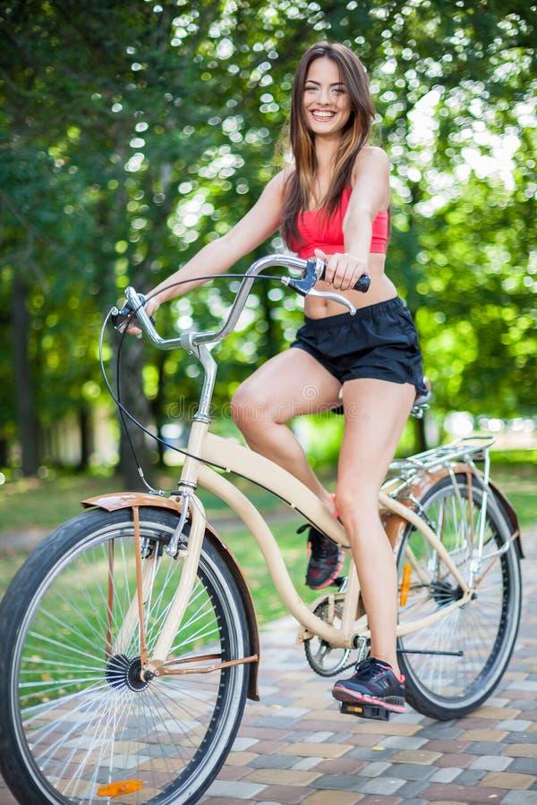 Молодая красивая девушка с велосипедом стоковые изображения rf