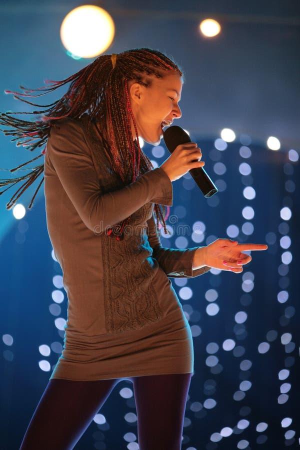 Молодая красивая девушка с микрофоном в руке стоковое изображение rf