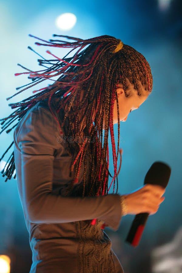 Молодая красивая девушка с микрофоном в руке стоковое изображение