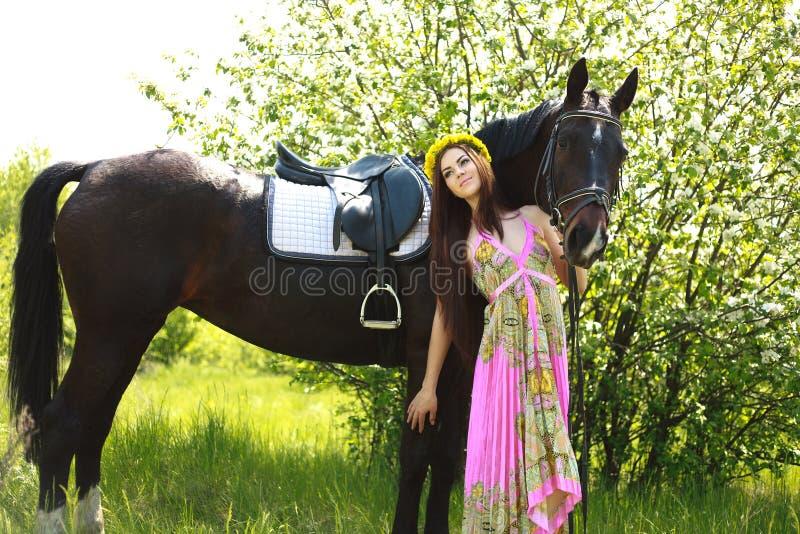 Молодая красивая девушка с лошадью в саде стоковое изображение rf