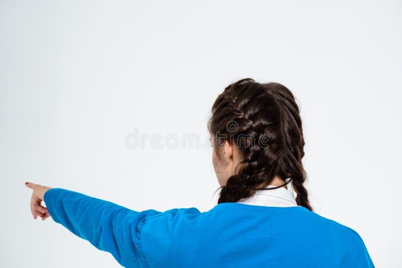 Молодая красивая девушка указывая палец прочь над белой предпосылкой стоковые фото