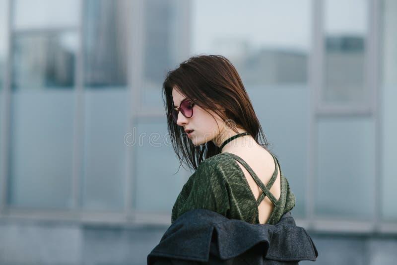 Молодая красивая женщина брюнет представляя на камере подвергая действию их задние части против фона современной архитектуры стоковые изображения