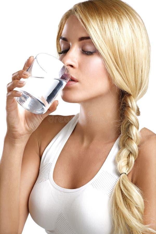 Молодая красивая женщина выпивая стекло воды стоковые фотографии rf