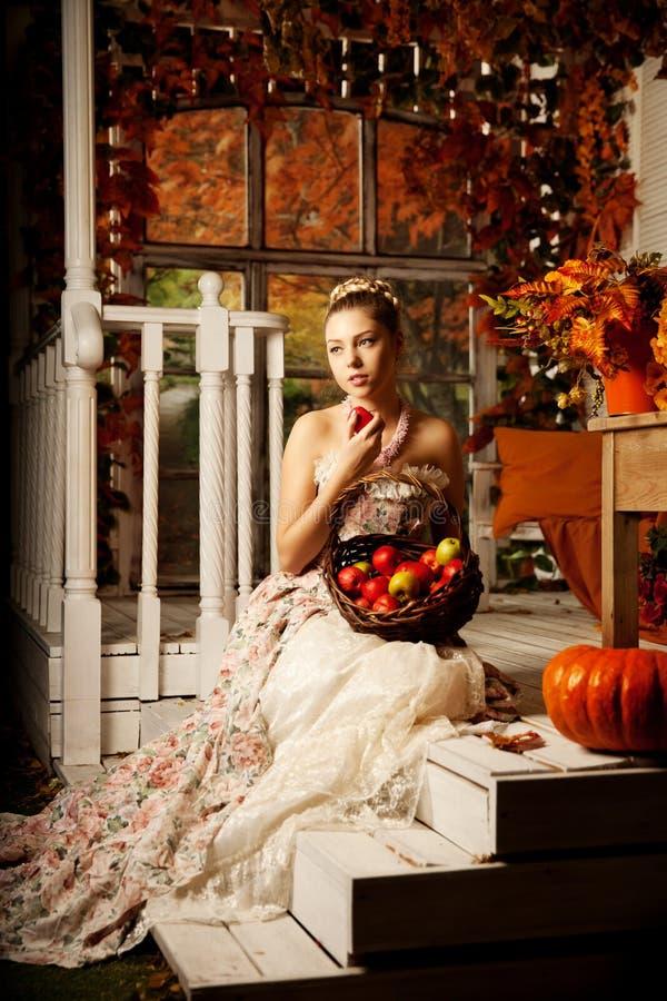 Молодая красивая женщина в винтажном платье на крылечке осени Красота g стоковые фотографии rf