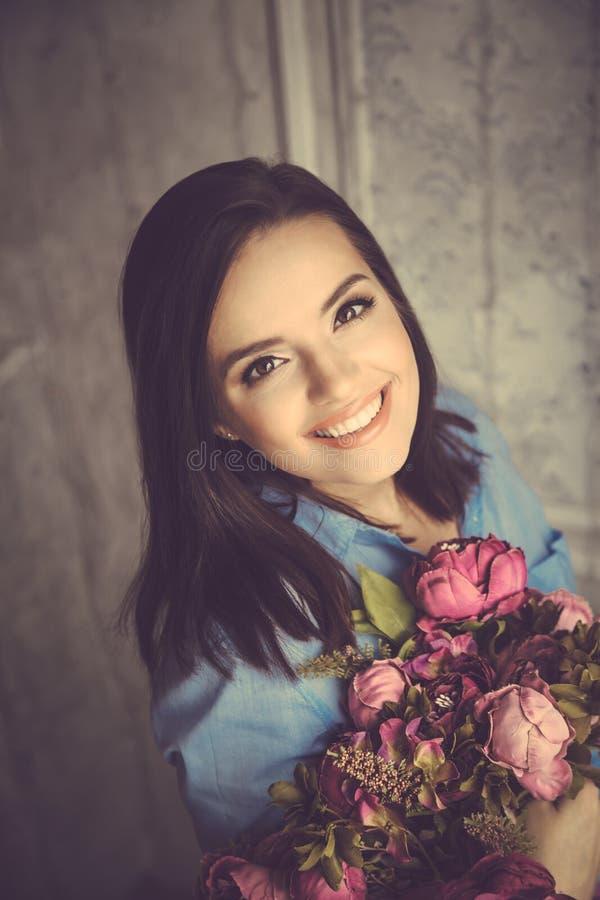 Молодая красивая женщина в голубой рубашке держа пук фиолетовой подачи стоковые изображения rf