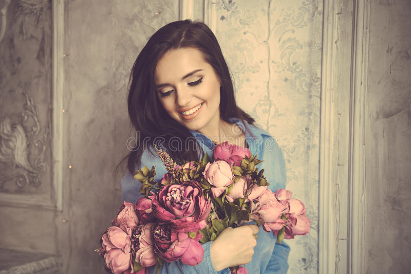 Молодая красивая женщина в голубой рубашке держа пук фиолетовой подачи стоковое фото