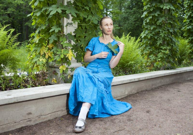Молодая красивая женщина в голубом платье в беседке скрутила зеленый вьюнок стоковые фотографии rf