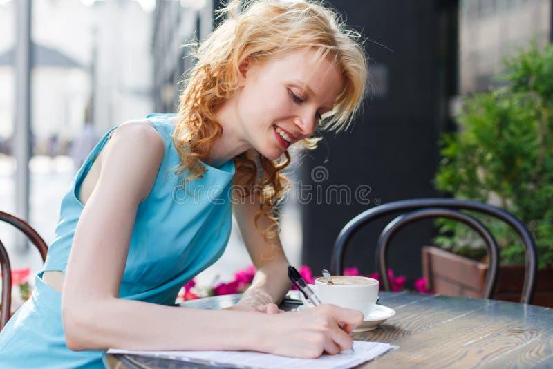 Молодая красивая женщина в голубом сочинительстве платья что-то в кафе стоковая фотография