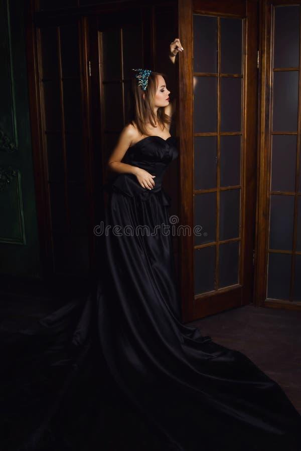Молодая красивая женщина в длинном черном платье и диамант увенчивают стоковая фотография