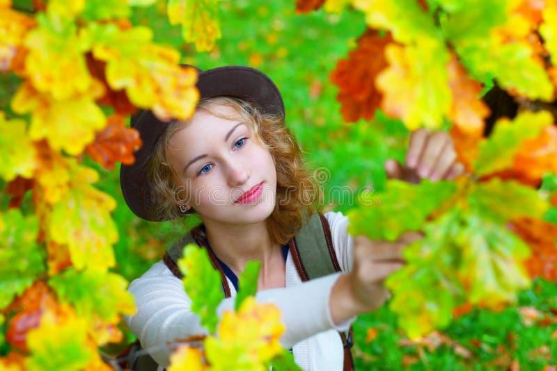 Молодая красивая женщина в листве осени стоковое фото rf