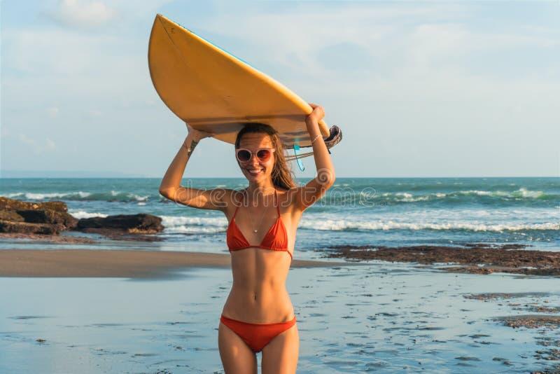 Молодая красивая женщина в красных стеклах бикини и солнца держит в руках прибой на пляже океана на заходе солнца стоковое фото rf