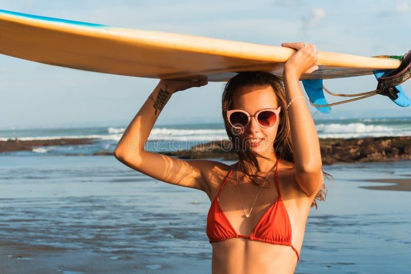 Молодая красивая женщина в красных стеклах бикини и солнца держит в руках прибой на пляже океана на заходе солнца стоковые изображения