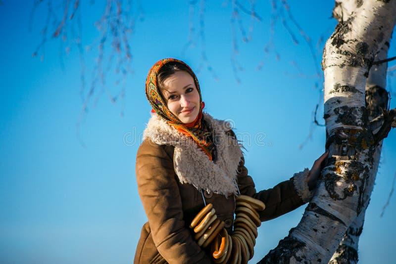 Молодая красивая женщина в национальной сюите на солнечной зиме стоковые фото