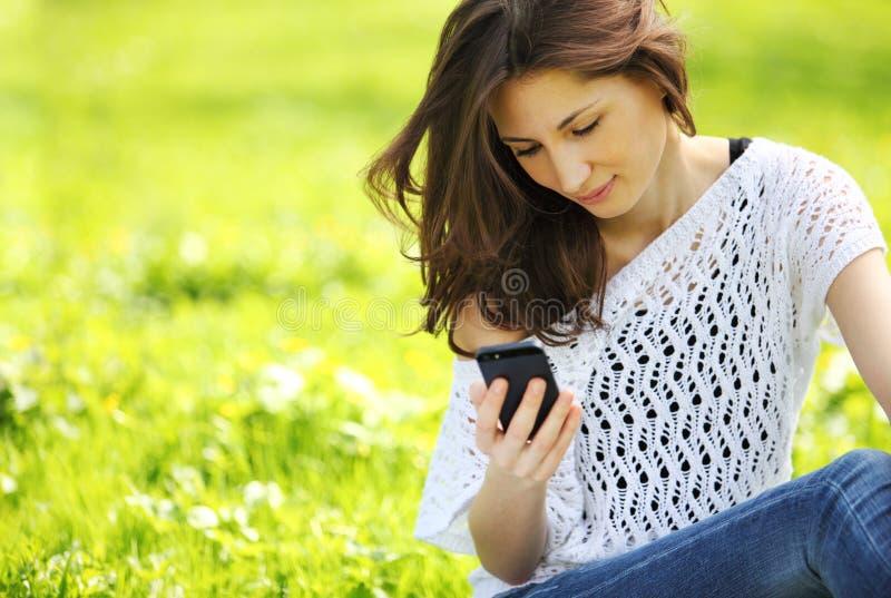 Молодая красивая женщина в парке лета читая сообщение стоковая фотография