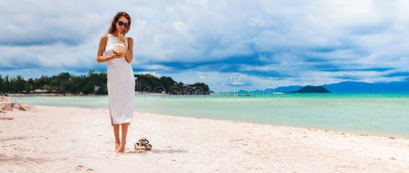 Молодая красивая женщина в платье, выпивая воде кокоса на тропическом пляже стоковые изображения