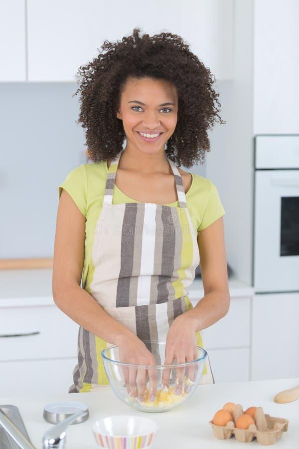 Молодая красивая женщина в рисберме делая торт стоковое фото