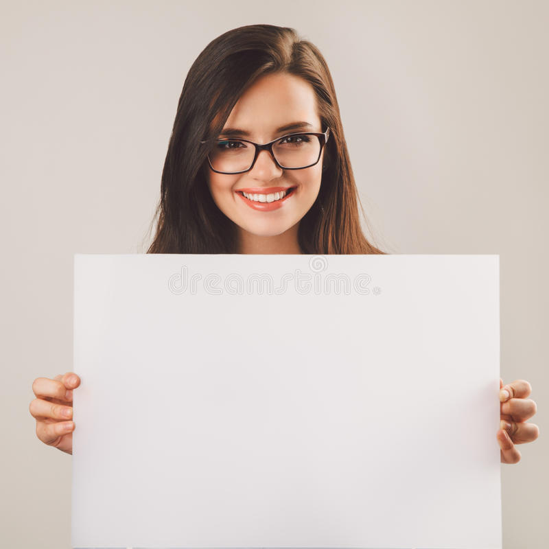Молодая красивая женщина в стеклах держа белую пустую доску стоковые фото