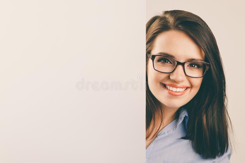 Молодая красивая женщина в стеклах держа белую пустую доску стоковые изображения