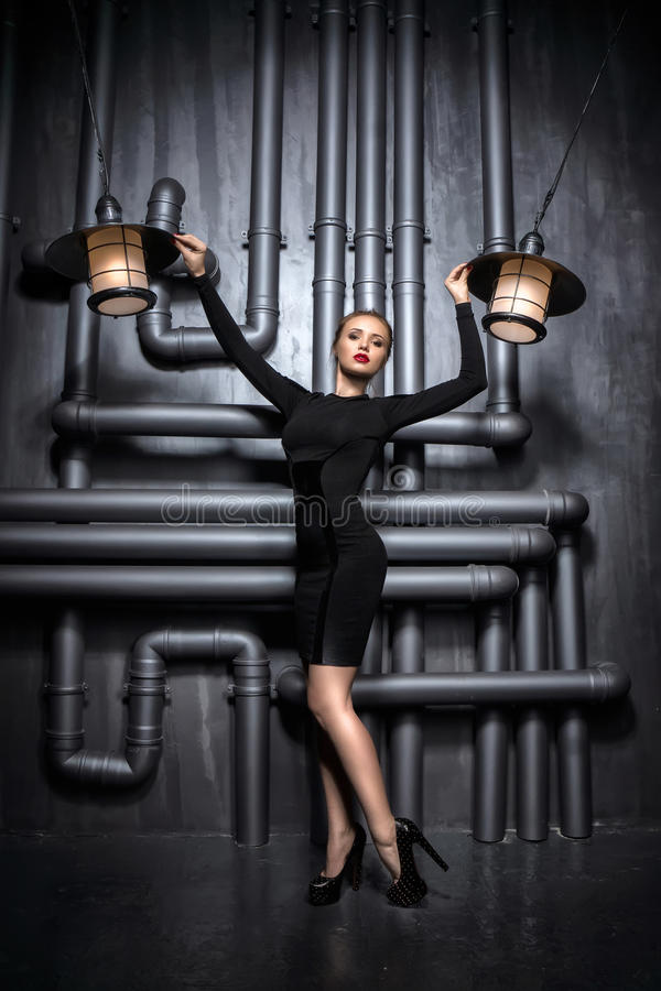 Молодая, красивая женщина в черном платье держа 2 ретро лампы стоковые фото