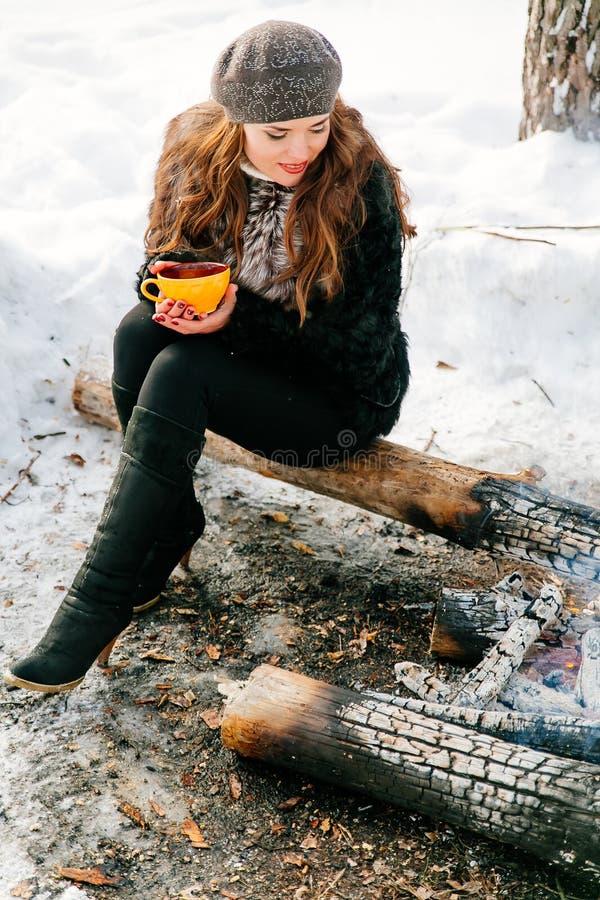 Молодая красивая женщина держа чашку чаю outdoors в зиме сидя на журнале около огня стоковые фотографии rf