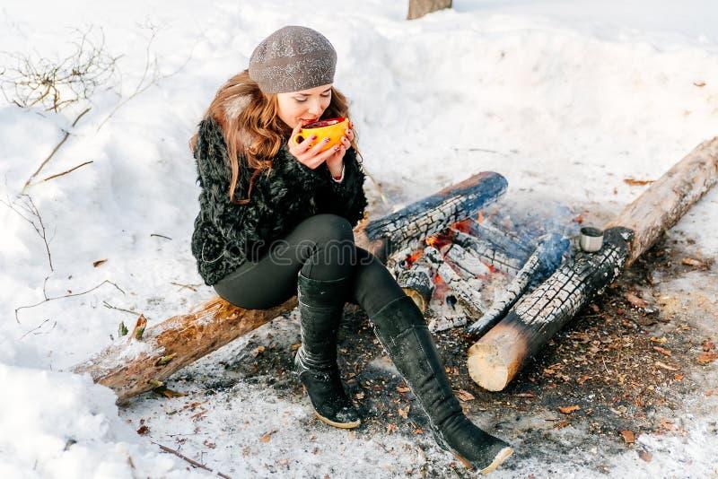 Молодая красивая женщина держа чашку чаю outdoors в зиме сидя на журнале около огня стоковые изображения rf