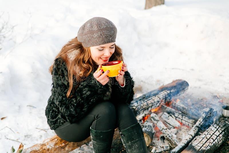 Молодая красивая женщина держа чашку чаю outdoors в зиме сидя на журнале около огня стоковое изображение
