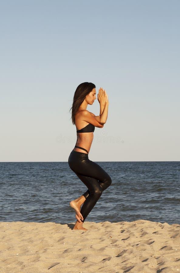 Молодая красивая женщина делая йогу на пляже в черном костюме спорта стоковые фотографии rf