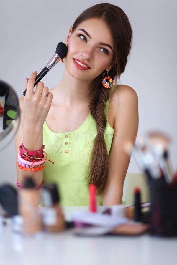 Молодая красивая женщина делая состав около зеркала стоковое фото rf