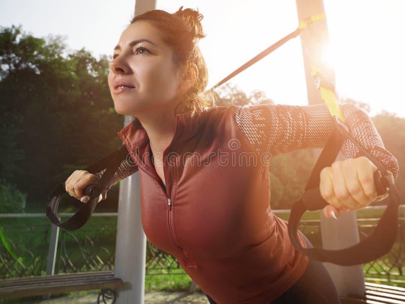 Молодая красивая женщина делая тренировку фитнеса с ремнями подвеса стоковое изображение rf