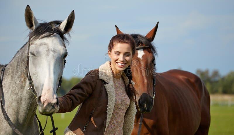 Молодая красивая женщина и 2 лошади стоковые фотографии rf
