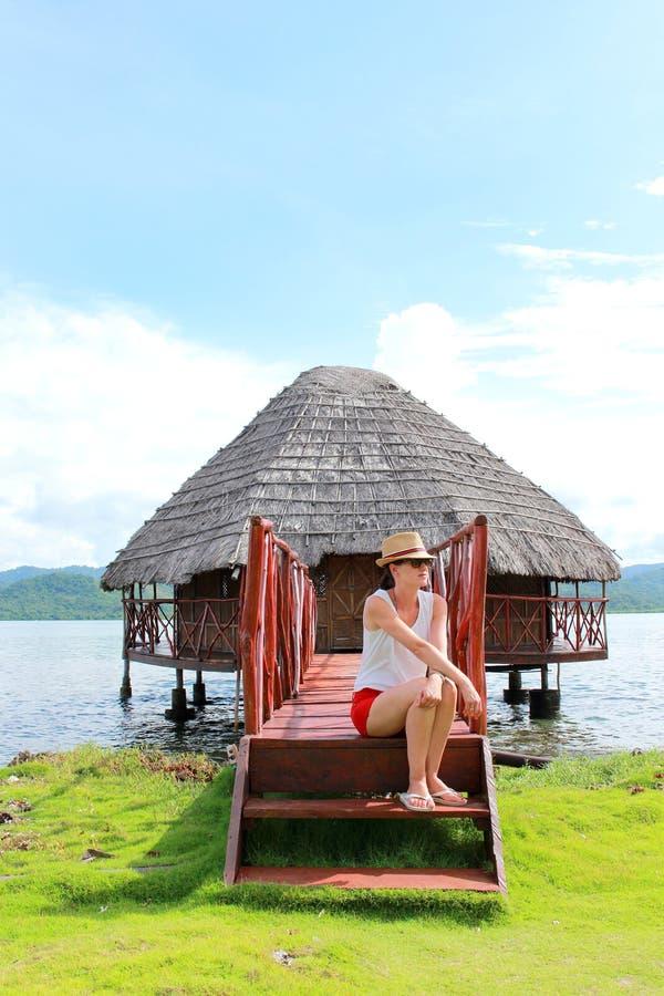 Молодая красивая женщина наслаждаясь ее временем и отдыхая близко к морю стоковое фото rf
