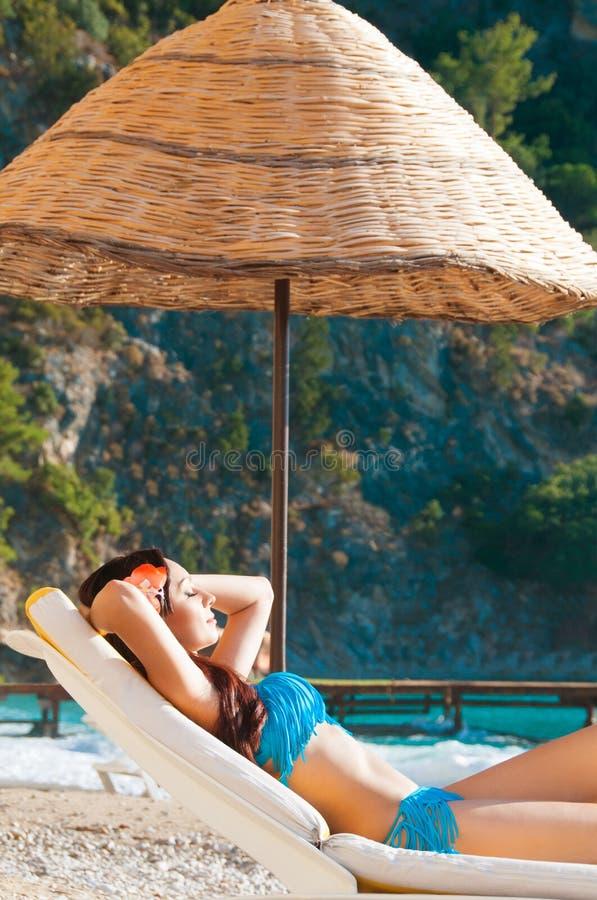 Молодая красивая женщина наслаждаясь на пляже лежа на шезлонге стоковая фотография rf
