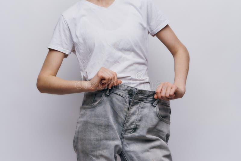 Молодая красивая женщина на светлой предпосылке, диета, потеря веса, прогресс, успех стоковая фотография