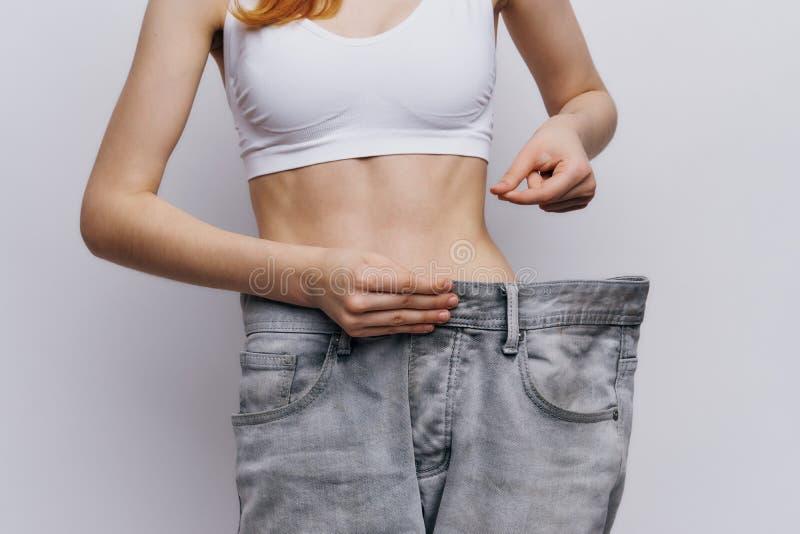 Молодая красивая женщина на светлой предпосылке, диета, потеря веса, прогресс, успех стоковое изображение rf