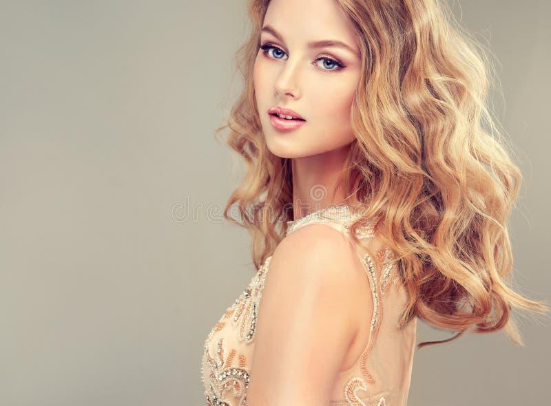 Молодая красивая женщина, одетая в мантии вечера стоковое фото