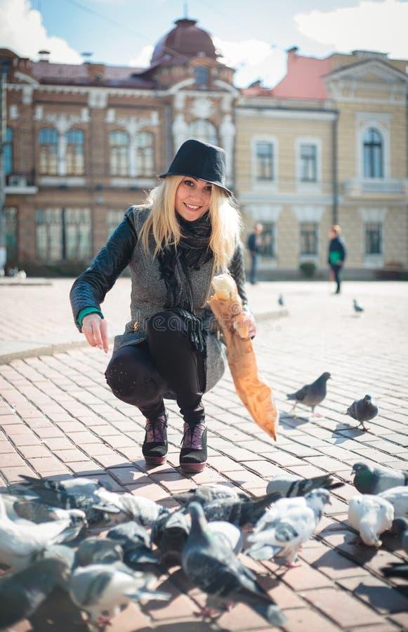 Молодая красивая женщина подает голуби с мякишами хлеба в городской площади стоковые изображения rf