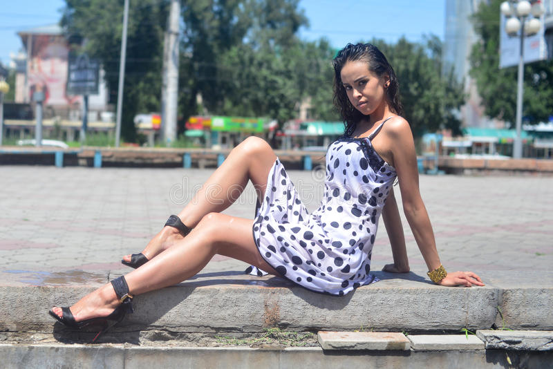Молодая красивая женщина представляя частично влажное усаживание на городском ландшафте стоковое фото rf