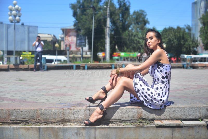 Молодая красивая женщина представляя частично влажное усаживание на городском ландшафте стоковая фотография rf