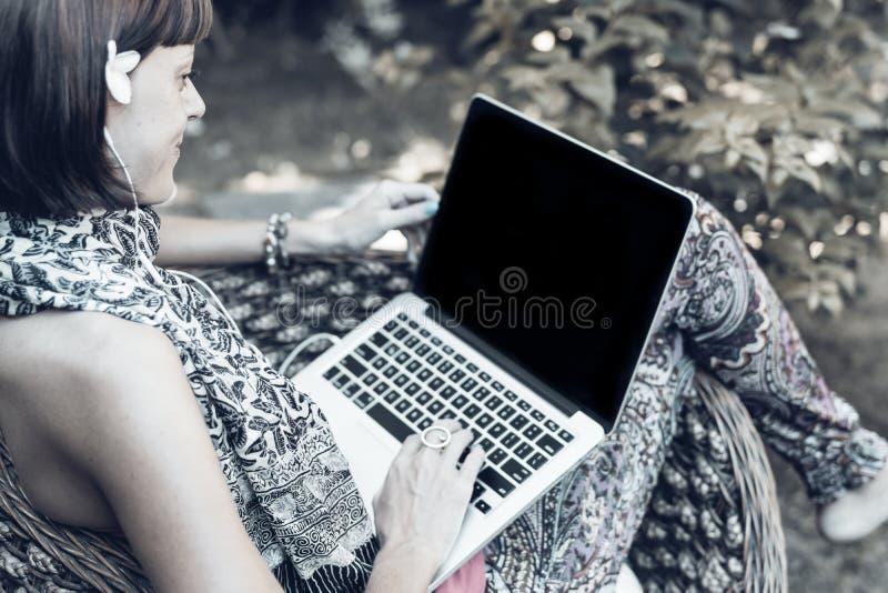 Молодая красивая женщина работая с компьтер-книжкой на внешнем тропическом парке, улыбке и счастливом расслабляющем чувстве в утр стоковое фото