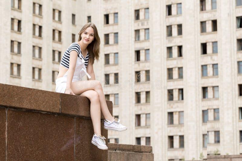Молодая красивая женщина сидя на лестницах около университета стоковые фото