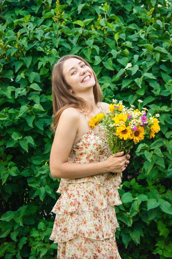 Молодая красивая женщина с букетом полевых цветков на лете стоковое фото rf