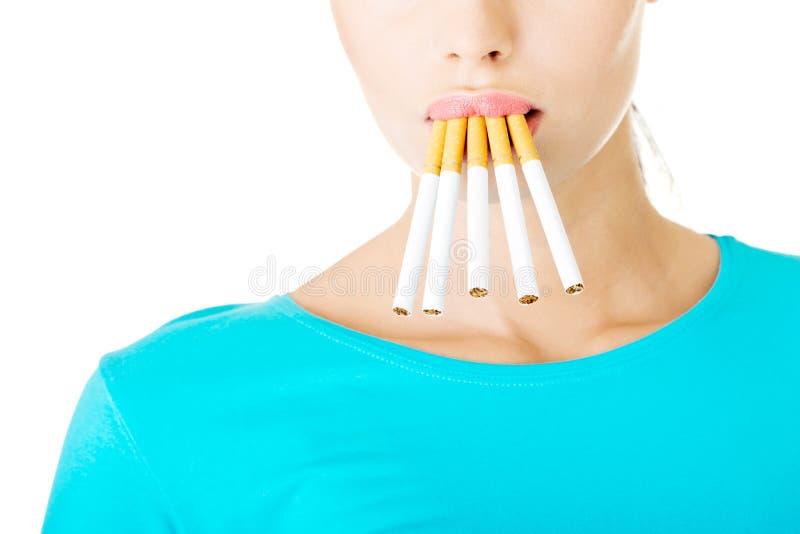 Молодая красивая женщина с сигаретами в рте. стоковая фотография