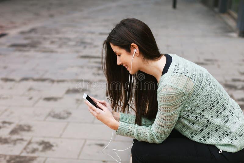 Молодая красивая женщина слушая к музыке с телефоном внутри outdoors стоковая фотография